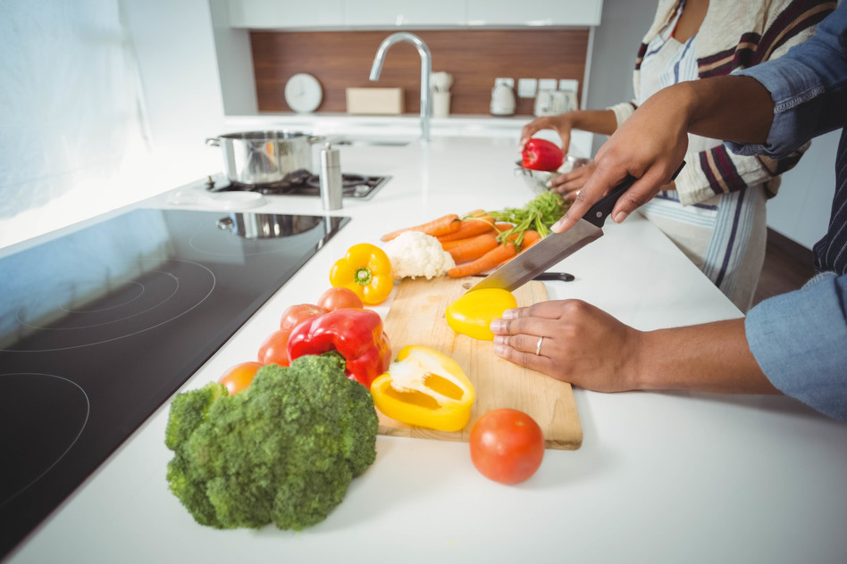 Mid section of couple preparing vegetables in the kitchen