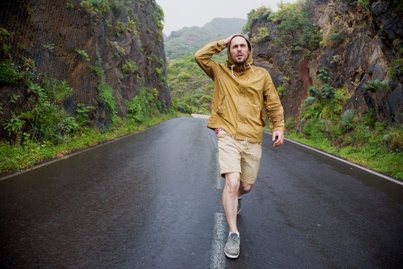 Young man walking down roadway on rainy day