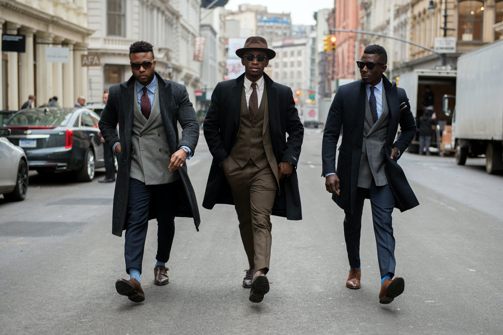 classy black men in suits walking on the street
