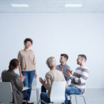 Happy woman talking in front of group during psychotherapy group therapy