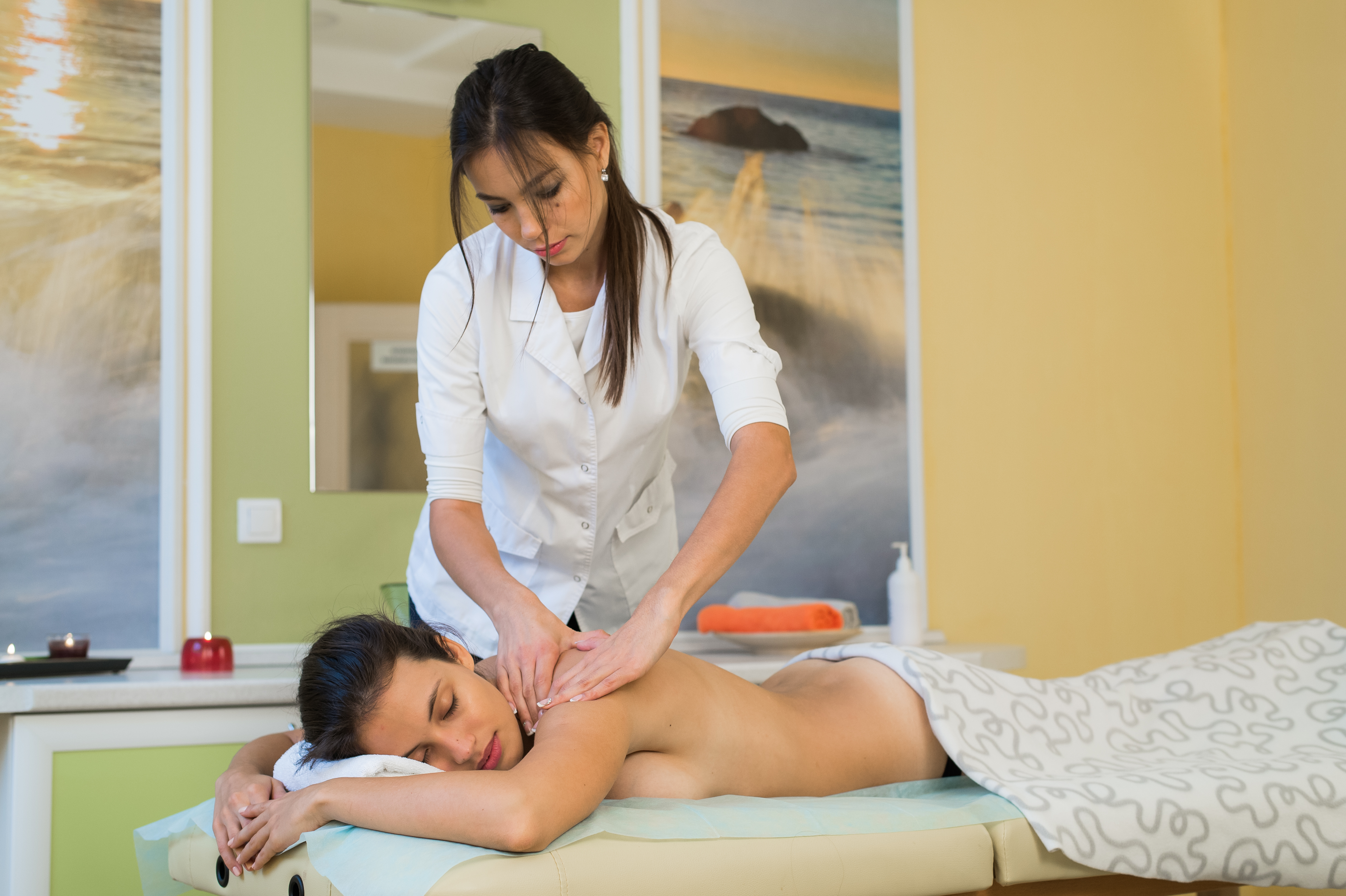 young woman enjoying back massage in beauty spa salon