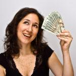 smiling happy woman with a bunch of money, twenty dollar bills