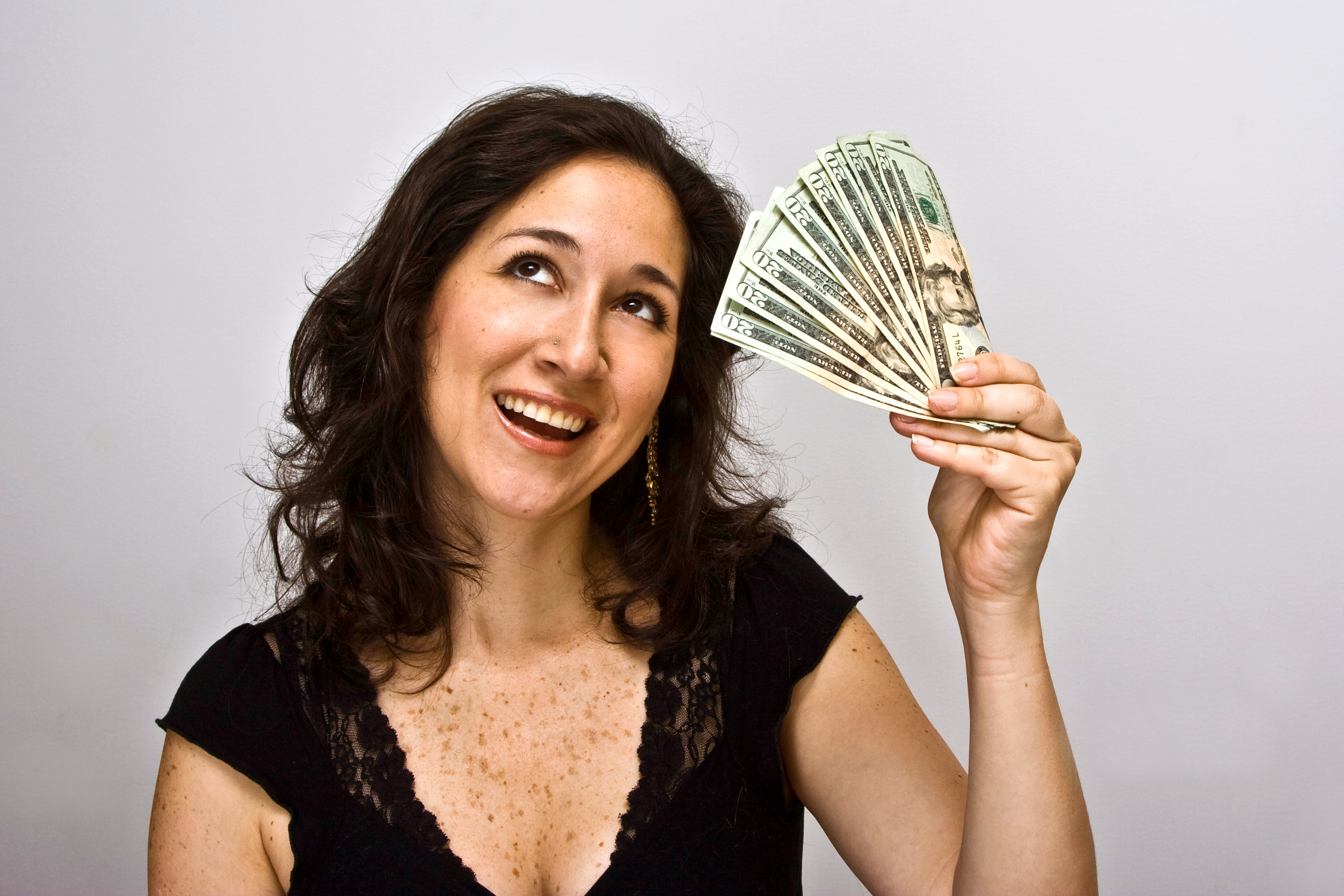 smiling happy woman with a bunch of money, twenty dollar bills